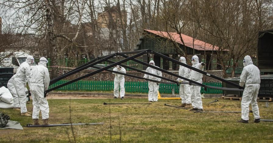Латвийские военные разворачивают специальную палатку.